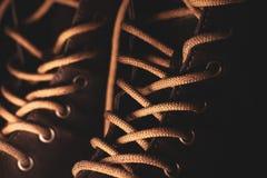Los cordones en las botas de cuero se cierran para arriba en fondo oscuro foto de archivo libre de regalías