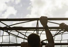 Los corredores de raza del fango están derrotando obstáculos usando cuerdas Detalles de las manos fotografía de archivo