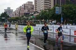 Los corredores esprintan abajo del estiramiento final del camino en el maratón 2017 del International de Taipei Imagen de archivo