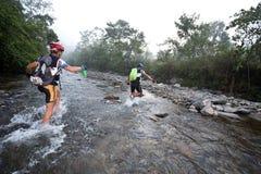Los corredores hacen manera a través de un río por la mañana Fotografía de archivo
