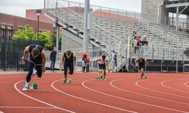 Los corredores masculinos de la High School secundaria salen los bloques Foto de archivo libre de regalías