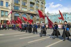 Los cosacos con las banderas abren la procesión del ` inmortal del regimiento del ` Día de la victoria en St Petersburg Foto de archivo libre de regalías