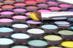 Los cosméticos aplican con brocha en los sombreadores de ojos imagenes de archivo