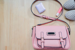 Los cosméticos y los accesorios del ` s de las mujeres empaquetan los zapatos rosados en el tablero de madera Fotos de archivo libres de regalías