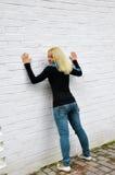 Los costes de la muchacha sobre una pared blanca Foto de archivo