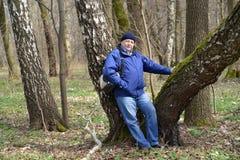 Los costes mayores del hombre que se inclinan contra un abedul en la madera de la primavera Fotografía de archivo
