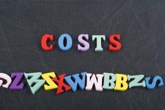 Los costes redactan en el fondo negro del tablero compuesto de letras de madera del ABC del bloque colorido del alfabeto, copian  Imágenes de archivo libres de regalías