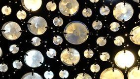 Los cristales tallados ronda grande brillan intensamente en una lámpara del metal, metrajes