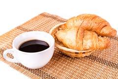 Los croissants franceses frescos y sabrosos en una cesta y una taza de café sirvieron Imagen de archivo libre de regalías