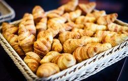 Los cruasanes frescos en una cesta en comida fría alinean Fotos de archivo