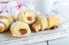 Los cruasanes hechos en casa con la fruta atascan, adornado con el azúcar en polvo con una taza de té de la mañana Fotos de archivo libres de regalías