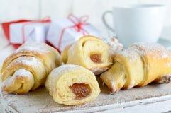 Los cruasanes hechos en casa con la fruta atascan, adornado con el azúcar en polvo con una taza de té de la mañana Imágenes de archivo libres de regalías