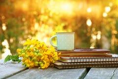 los cuadernos al lado del campo florecen en la tabla de madera al aire libre Fotos de archivo libres de regalías