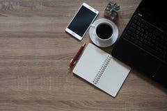 Los cuadernos, las plumas, el café, los teléfonos móviles y el ordenador portátil se colocan en la tabla de madera Imágenes de archivo libres de regalías