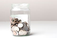 Los cuartos 25 centavos cambian monedas en un tarro de cristal Imágenes de archivo libres de regalías