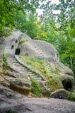 Los cuartos tallaron en la roca con las puertas y las ventanas en el monasterio de la cueva en las colinas cárpatas Rozhirche Imagenes de archivo