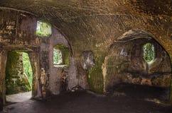 Los cuartos tallaron en la roca con las puertas y las ventanas en el monasterio de la cueva en las colinas cárpatas Rozhirche Imagen de archivo