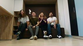 Los cuatro amigos felices comenzaron a ver la TV juntos Amistad y concepto del entretenimiento almacen de metraje de vídeo