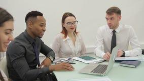 Los cuatro empresarios se preparan para la localización de la presentación en la tabla grande en oficina brillante metrajes