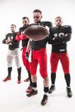 Los cuatro jugadores de fútbol americano que presentan con la bola en el fondo blanco imagenes de archivo