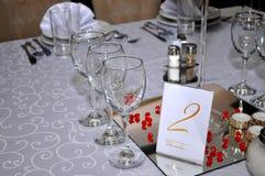 Los cubiertos con las flores coloridas, la joyería y las velas perfumadas se ponen en las mesas redondas para las bodas tradicion Fotografía de archivo libre de regalías