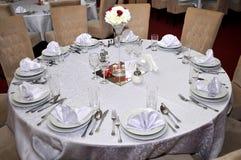 Los cubiertos con las flores coloridas, la joyería y las velas perfumadas se ponen en las mesas redondas para las bodas tradicion Imagen de archivo