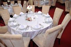 Los cubiertos con las flores coloridas, la joyería y las velas perfumadas se ponen en las mesas redondas para las bodas tradicion Fotografía de archivo