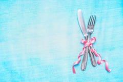 Los cubiertos fijaron con la cinta rosada en el fondo azul claro, visión superior, lugar para el texto Imagenes de archivo