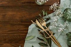 Los cubiertos planos del oro de la endecha, flores, anillos en la servilleta de lino, casandose concepto, día de fiesta florecen  Fotografía de archivo
