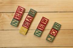 Los cubos de madera en la tabla de madera con trabajo del Año Nuevo de las palabras nuevo se refrescan Fotos de archivo