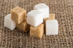 Los cubos del azúcar marrón y blanco en yute empaquetan Imagenes de archivo