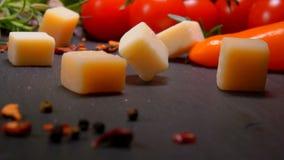 Los cubos del queso parmesano bajan a la superficie de la tabla almacen de metraje de vídeo