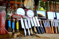Los cuchillos viejos del vintage, botella, duplican en fila en un mercado callejero en la ciudad - venta de objetos del vintage imagen de archivo libre de regalías