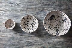Los cuencos de cerámica de diversos tamaños están vacíos en un fondo de madera gris Endecha plana de los platos de porcelana hech imagenes de archivo