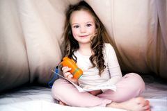 Los cuentos de hadas de lectura de la niña reservan bajo cubiertas en la tarde con la linterna imagen de archivo libre de regalías
