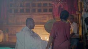Los curadores tradicionales fumigan al hombre con incienso mientras que curan ceremonia en casa mágica del pueblo Ritual curativo almacen de video