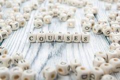 Los cursos redactan escrito en el bloque de madera ABC de madera Imágenes de archivo libres de regalías