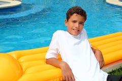 Los días de fiesta de las vacaciones del adolescente del muchacho se basan sobre el flotador de la piscina Imágenes de archivo libres de regalías