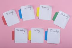 Los días de la semana - las etiquetas engomadas de papel atadas al fondo rosado fotos de archivo