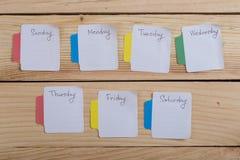 Los días de la semana - las etiquetas engomadas de papel atadas al tablero son imagen de archivo