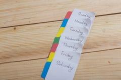 Los días de la semana - las etiquetas engomadas de papel atadas al tablero son foto de archivo