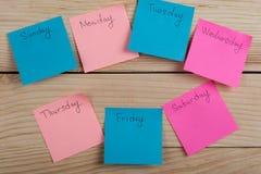 Los días de la semana - las etiquetas engomadas de papel atadas al tablero son imagenes de archivo
