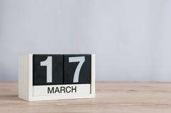 Los días felices del St Patricks ahorran la fecha 17 de marzo Día 17 del mes, calendario de madera en fondo ligero El tiempo de p Fotografía de archivo