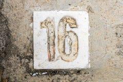 Los dígitos con hormigón en la acera 16 Imagen de archivo libre de regalías