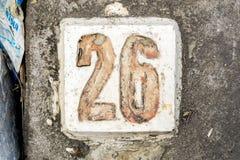 Los dígitos con hormigón en la acera 26 Imagen de archivo libre de regalías