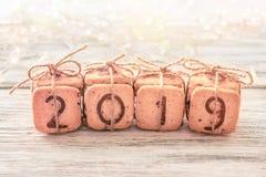 Los dígitos festivos 2019 de la Navidad del regalo hicieron de las galletas en el fondo blanco con las luces y el bokeh Confectio fotografía de archivo