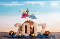 Los dígitos 2017 trenzaron con guita, el coco con la paja y los paraguas Imagen de archivo libre de regalías