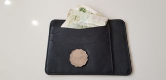 Los dólares de Hong-Kong acuñan ponen en la cartera de cuero negra con un billete de banco del yuan imagen de archivo
