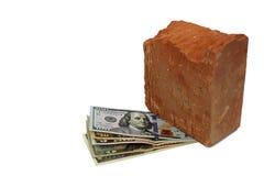 Los dólares se presionan con un pedazo de piedra Foto de archivo libre de regalías