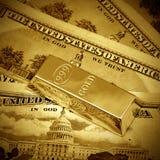 Los dólares y el lingote de oro Foto de archivo